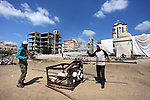 Palestinian workers remove the rubbles from el-katiba building that was damaged in an Israeli airstrike in Gaza City, on August 15, 2018. Photo by Mahmoud Ajour