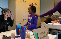 NWA Democrat-Gazette/CHARLIE KAIJO Andrew Dunlap, play facilitator, (left) helps Amari Williams 7, of Centerton make a noise maker during the Zing in The New Year! event on Sunday, December 31, 2017 at Amazeum in Bentonville. Visitors wrote down New Year's wishes and made party hats and noise makers  and enjoyed the general activities