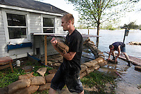 John Gamage, left, and Ryan Hallam sandbag the home at 1207 North Main Street in order to protect the home from four feet of Mississippi River floodwater in the Red Star District of Cape Girardeau, MO, on Thursday, April 28, 2011.