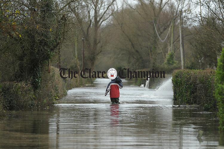 A T cameraman heads off through flood water at Springfield Clonlara. Photograph by John Kelly.