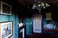 A Japanese wedding dress hangs on the back of the dining room door echoing the lines of the 'draped fabric' wallpaper by Zuber