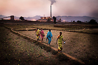Women walk through a field in front of the Vedanta Alumina plant in Lanjigarh. The huge bauxite deposits in the Niyamgiri hills have led the Vedanta group to set up an alumina refinery at Lanjigarh, making the local population of Dongria Kondh tribespeople fearful for their future. Vedanta Resources has come under immense pressure from human rights and environmental groups to abandon its plans to mine at the Niyamgiri mountains, as the site is considered sacred by the local tribal community....