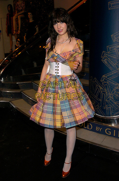 "DAISY LOWE.At the ""Giles Gold for New Look"" Launch Party,.New Look, Oxford Street, London, England, .March 12th 2007..full length blue red orange tartan plaid dress white waist belt red shoes tights holding glass drink cocktail.CAP/CAN.©Can Nguyen/Capital Pictures"