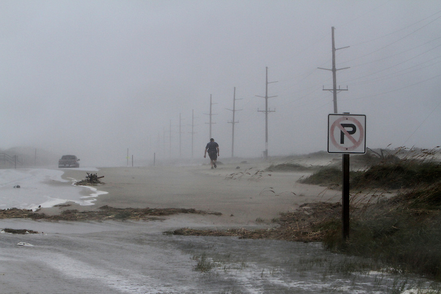 Ron Brietharp, 48, of Buxton, NC, walks into a nearly 80-mile-per-hour headwind to rescue his fiance's truck that got stuck in the sand and salt water covering N.C. 12 just north of Hatteras Village during Hurricane Irene on Saturday, Aug. 27, 2011.  The spot where the ocean broke through the dunes is near where Hurricane Isabel cut a new inlet in 2003.  Brietharp's fiance was earlier helped away from the truck and the dangerous situation by police.  Photo by Ted Richardson