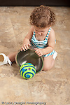 13 month old baby girl at home Piaget object permanence looking for and finding toy ball hidden under metal bowl vertical