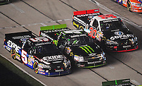 Nov. 6, 2009; Fort Worth, TX, USA; NASCAR Camping World Truck Series drivers Mike Skinner (5), Ricky Carmichael (4) and Todd Bodine (30) go three wide down pit road during the WinStar World Casino 350 at the Texas Motor Speedway. Mandatory Credit: Mark J. Rebilas-