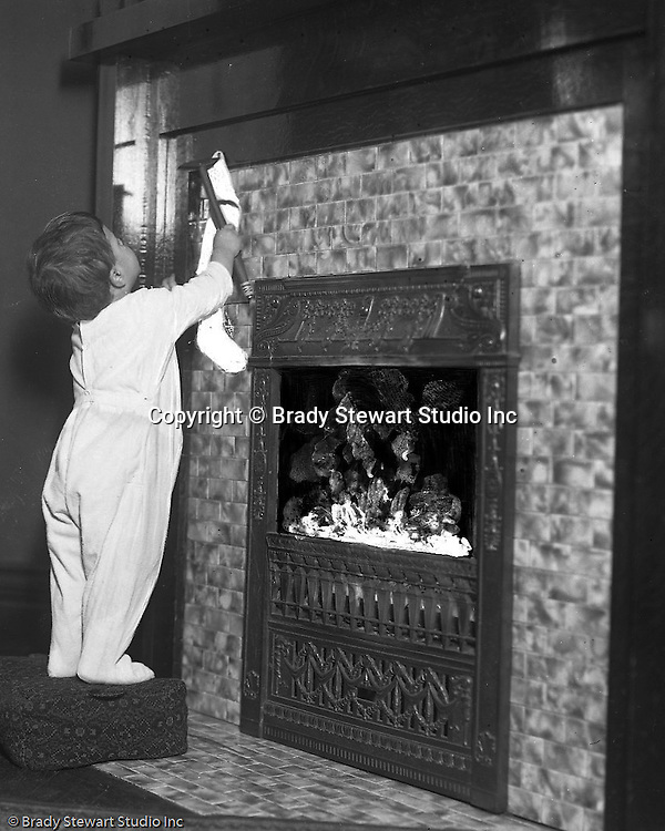 "Wilkinsburg PA:  Helen Stewart hanging a Christmas Stocking - 1918.  Brady Stewart etched on the emulsion side of the film to create a ""fire"" effect in the fireplace."
