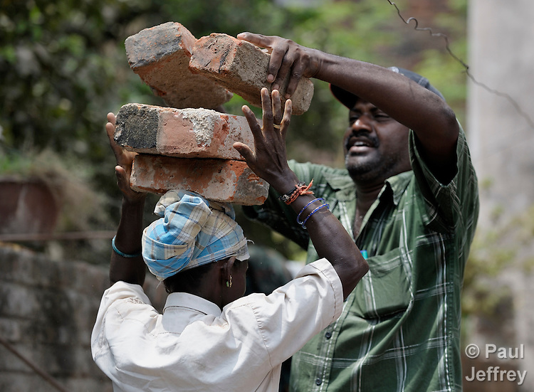 A woman carries bricks that a man places on her head while working on a construction site in the village of Kundrathur Somangalam in southern India's state of Tamil Nadu.