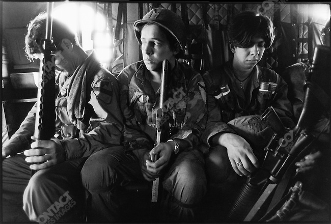 Three members of a 1st Air Cavalry unit on board a Chinook helicopter, taking them from their basecamp to the insertion point where their field mission will start.  Near Xuan Loc, South Vietnam, December 1971