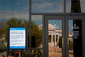 The Smithsonian National Gallery of Art is reflected in the glass doors of the Smithsonian National Air and Space Museum, and a sign is posted to inform people that the museum is closed as the United States deals with the COVID-19 pandemic in Washington, DC, Tuesday, March 17, 2020. Credit: Rod Lamkey / CNP