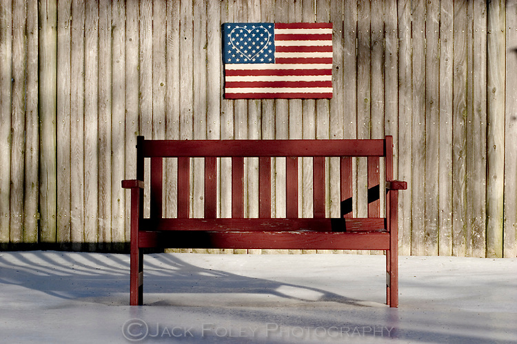 American flag with a heart of lights in the star area, on a fence in a yard, with a bench frozen in ice and snow.