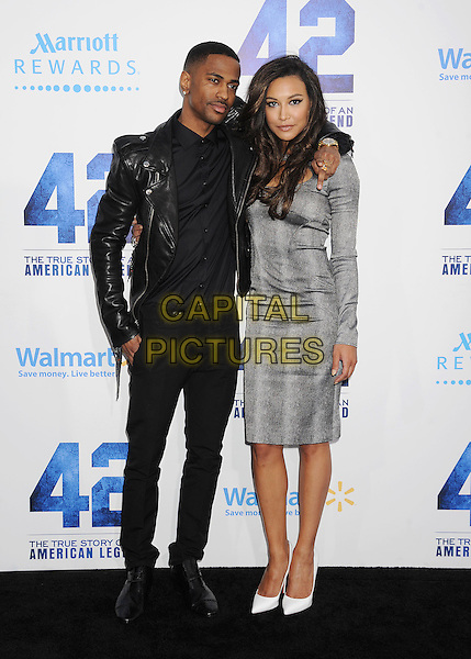 "Sean Michael Anderson (Big Sean) & Naya Rivera.""42"" Los Angeles Premiere held at the TCL Chinese Theatre, Hollywood, California, USA..April 9, 2013.full length dress grey gray pattern cut out away black leather jacket top white shoes arm over shoulder couple .CAP/ROT/TM.©Tony Michaels/Roth Stock/Capital Pictures"