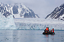 Tourists in zodiac cruising in front of large glacier at the end of fiord, June, Svalbard, Norway