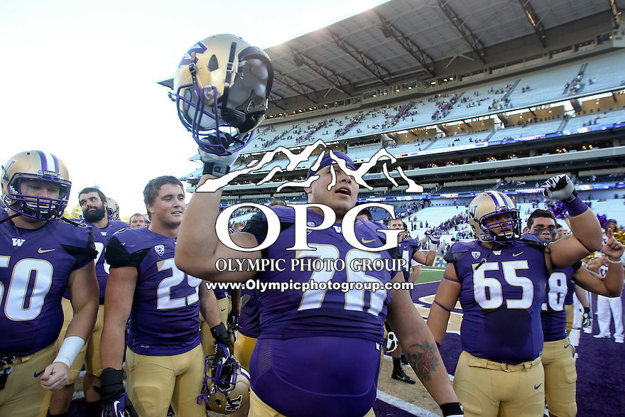Sept 20, 2014:  Washington's #76 Dexter Charles sings the school fight song with teammates to the fans after the game against Georgia State.  Washington defeated Georgia State 45-14 at Husky Stadium in Seattle, WA.