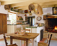 This country kitchen has an open fireplace and a simple scrubbed wooden table for dining