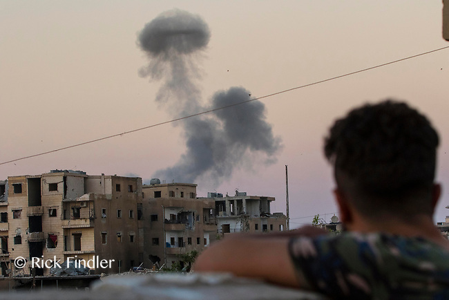 August 2017. Raqqa, Syria.<br /> Smoke rises from a building believed to be housing ISIS, after being hit by a mortar round fired from a United States military base in western Raqqa.<br /> The MFS (Syriac Military Council) are a group of Assyrian Christians who fight alongside the Syrian Democratic Forces in the fight to topple ISIS.<br /> Photographer: Rick Findler