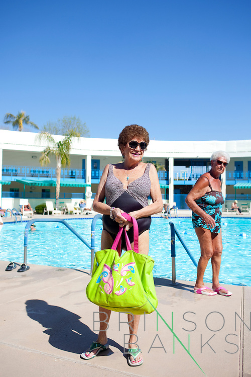 "Jean Snell, a Sun City resident for the past 27-years, poses for a portrait as her friend Esther Klepacz puts on her flip-flops after some time in the pool at the Lakeview Recreation Center in Sun City, Arizona March 12, 2010. Jean is originally from Michigan and Esther from Ohio and the sunshine in Sun City brings the two to the pool just about every day. They walk back and forth in the pool with friends every day. ""We're kind of a little clique here-- a little sewing club,"" Esther says. They walk back and forth in the warm pool until ""our jaws get tired,"" Esther says. The group talks about food mostly, and who is taking what pills, she said..2010 marks Sun City the first planned retirement city in the United States' 50th anniversary."