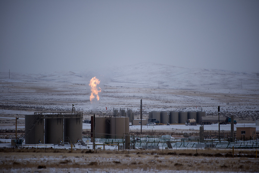 "Natural gas released as a byproduct of oil drilling burns off near petrolium storage tanks outside of Douglas, Wyo., Thursday, November 22, 2013. The state will require pre-drilling testing of groundwater at sites where hydraulic fracturing, also known as ""fracking"" is used. (Kevin Moloney for the New York Times)"