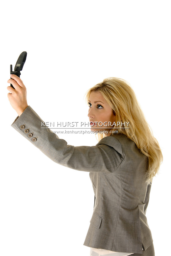Beautiful blonde woman is holding a cellphone extended as if trying to get a better wireless signal.