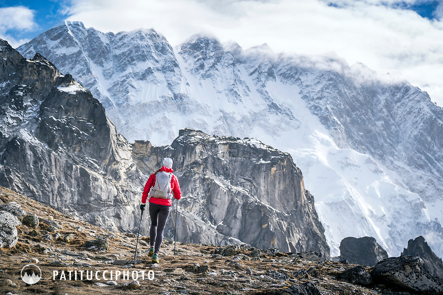 A trail runner heading up the first of 3 Passes, Kongma La, while running the 3 Passes tour in the Khumbu Valley, Nepal. In the background is Nuptse.