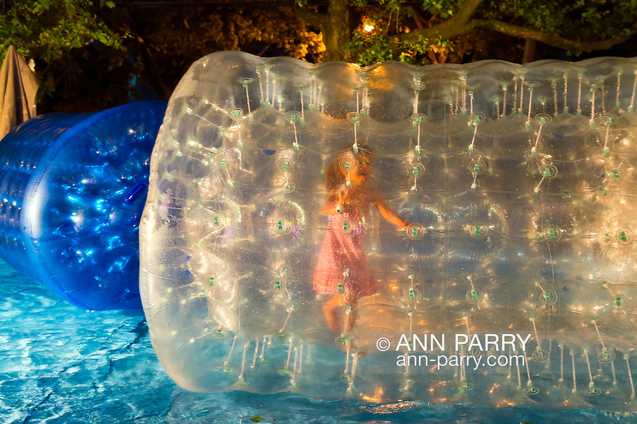 Young girl inside Bobbles roller tube is walking and rolling on water, during the first night of the annual Herricks Community Fund Spring Carnival, which raises funds for programs that enrich the community and school district. The Long Island carnival runs through June 2.
