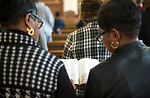WATERBURY, CT-012119JS07- Guests share a bible as they read from the scripture during the annual Rev. Martin Luther King Day Service held Monday at Grace Baptist Church in Waterbury. During the event, which was hosted by the Waterbury Fellowship of Christian Churches, former Waterbury Police Chief Vernon L. Riddick, Jr.,  was honored with the MLK Achievement Award. <br /> Jim Shannon Republican American