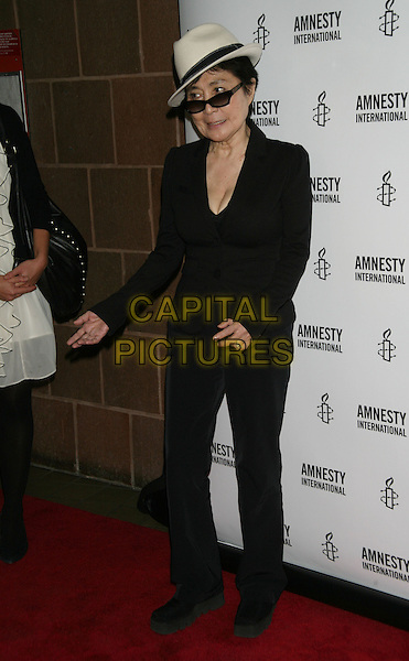 """YOKO ONO.The New York Premiere of """"Nowhere Boy"""" at the Tribeca Performing Arts Center, New York, NY, USA..September 21st, 2010.full length black suit jacket trousers white cream fedora trilby hat sunglasses shades hands.CAP/LNC/TOM.©TOM/LNC/Capital Pictures."""