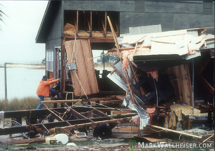 A Wakulla Co. man climbs into his destroyed waterfront home after Hurricane Kate November 21, 1985.  Kate, a late November Hurricane,  was latest forming Atlantic hurricane on record at the time and was the second for the area following Hurricane Elena two months earlier.