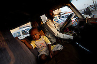 a somali refugee drives back from work on a  rrented public mini bus carrying his son next to him in  the Besateen Shanty town in Aden, Yemen on Monday November the 26th 2007.///..Ever since the collapse of the Siad Barre regime in 1991 Somali men, women and children have been arriving at the port of Bosasso to buy passage in small open fishing boats to Yemen, where they are given automatic political asylum..The  boat trip, costing from 70 to 150 usd per person, can be often fatal due to the roughness of the sea, the overcrowded boats and the merciless of the smugglers..On the night of Nov 29 2007 a small fishing boat while trying to download it's load of refugees a few hundred meters from the Yemeni  shores of Meifa Haja, flipped over and was overwhelmed by the constant waves. of its 130 passengers, only 42 reached the UNHCR ( United Nations High Commissioner for Refugees )  refugee center in Meifa. 30 bodies where recovered the next day.  the rest are still unaccounted for.. UNHCR  estimates more than 80.000 somali refugees live  in the country residing mostly in shanty towns in Sana'a' and Aden.