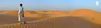 Tunisia, Ksar Ghilane, Sahara Desert, boy (13-14) looking at dunes, rear view, (Licence this image exclusively with Getty: http://www.gettyimages.com/detail/sb10065474cc-001 )
