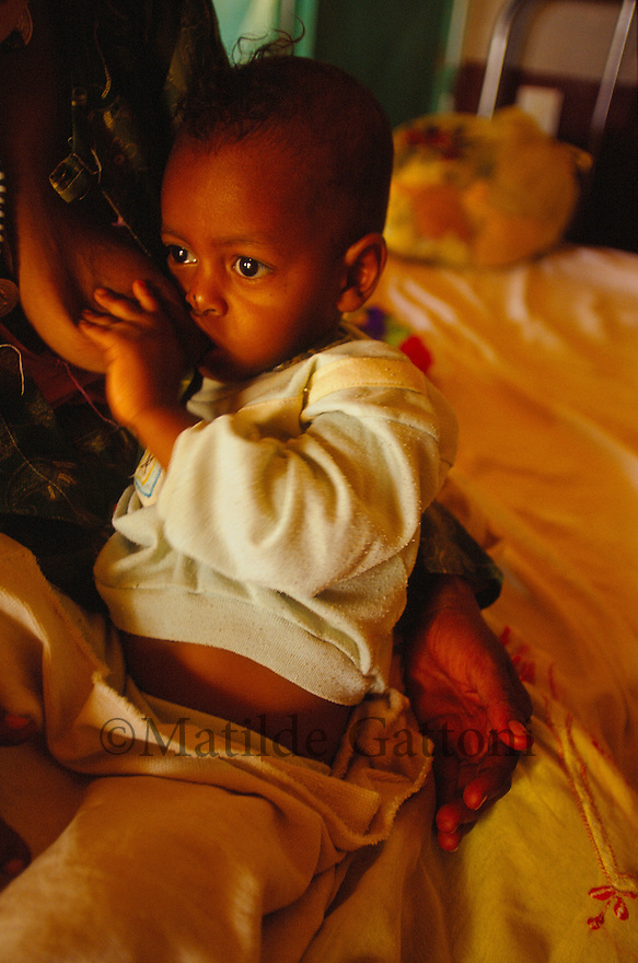 Eritrea - Gash Barka - Baby being breastfed by his mother in a small hospital for malnourished people. As a result of 30 years of war for independence against Ethiopia (from 1961 to 1991) and another 3 years from 1997 to 2000, there are 50,000 Eritreans currently living in internally displaced (IDP) camps throughout the country. These IDPs have fled three times in the last 10 years, each time because of renewed military conflict. They lived in relatives' homes when lucky enough, but mostly, the fled to the mountains, where they attempted to do what Eritreans do best, survive. Currently there is no Ethiopian occupation in Eritrea, but landmines prevent the IDPs from finally going home. .It is estimated that every Eritrean family lost two or three members to the war which makes the reality of the current emergency situation even more painful for Eritreans worldwide. Currently, the male population has been decreased dramatically, affecting the most fundamental socio-economic systems in the country. Among the refugee population, an overwhelming majority of families are female-headed, severely affecting agricultural production. For, IDPs in particular, 80% of households are female-headed..The unresolved border dispute with Ethiopia remains the most important drawback to Eritrea's socio-economic development, as national resources (human and material) continue to be prioritized for national defense. Eritrea is vulnerable to recurrent droughts and variable weather conditions with potentially negative effects on the 80 percent of the population that depend on agriculture and pastoralism as main sources of livelihood. The situation has been exacerbated by the unresolved border dispute, resulting in economic stagnation, lack of food security and increased susceptibility of the population to various ailments including communicable diseases and malnutrition. .