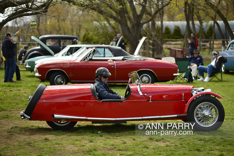 Floral Park, New York, U.S. - April 27, 2014 - Owner STEVE KAPLAN, in driver's seat, is about to drive his red BRA CX3, a custom Beribo Replica Automobiles kit vehicle with three wheels, and registered by DMV as a 2009 Custom Motorcycle, at the 35th Annual Antique Auto Show at Queens Farm.