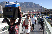 CAPE TOWN, SOUTH AFRICA - MARCH 20: Colored and black commuters rush to a taxi and train station on March 20, 2012 in Cape Town, South Africa. Most South African Colored and Blacks people doesn't live in or around the city. Many commute to vast townships and live in bad conditions. Many spend hours everyday to come to work and back. (Photo by Per-Anders Pettersson)