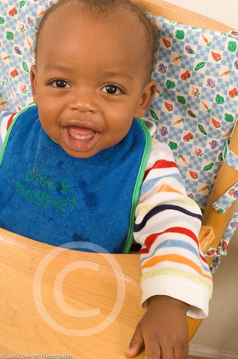 9 month old baby boy, portrait closoeup, wearing bib, in high chair
