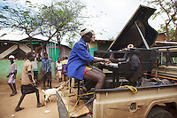"Ethiopia. Southern Nations, Nationalities, and Peoples' Region. Omo Valley. Turmi. Market day. Hamar tribe (also spelled Hamer). Pastoralist group. Toyota pick-up truck. Marc Vella is a french musician and a nomadic pianist. Over the last 25 years he has travelled with his Grand Piano in around forty countries to celebrate humanity. Thanks to the variacordes which he has devised, his piano music is unique. Creator of ""La Caravane amoureuse"" (The Caravan of Love) he takes people with him to say ""I love you"" to others and ""lovingly conquered"" their hearts and souls. Marc Vella and a Hamar man play an improvised duet-playing - one piano and four hands. The Omo Valley, situated in Africa's Great Rift Valley, is home to an estimated 200,000 indigenous peoples who have lived there for millennia. Amongst them are 60'000 to 70'000 Hamar, an Omotic community inhabiting southwestern Ethiopia. Southern Nations, Nationalities, and Peoples' Region (often abbreviated as SNNPR) is one of the nine ethnic divisions of Ethiopia. 9.11.15 © 2015 Didier Ruef"