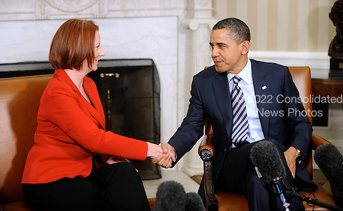 United States President Barack Obama checks hands with Prime Minister Julia Gillard of Australia in the Oval Office of the White House March 7, 2011 in Washington D.C..Credit: Olivier Douliery / Pool via CNP