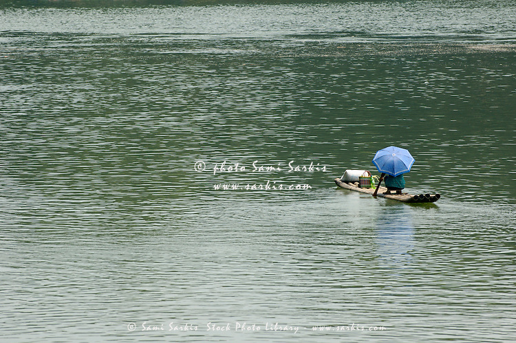 Person with sun umbrella travelling down a river on a bamboo raft, Fuli Village, Guangxi, China.