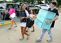NWA Democrat-Gazette/DAVID GOTTSCHALK   Stacy Parker (from left), carries items with her daughter Jade Schultz, an incoming freshman at the University of Arkansas, daughter Reagan Parker, 12, and Jade's boyfriend Gavin Cobb Thursday, August 10, 2017, into her Maple Hill campus housing at the University in Fayetteville. Students, including those in the University band and participating in sorority recruitment, had the opportunity to move in early.