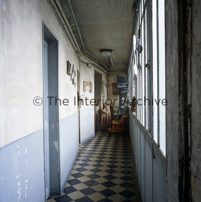 A hallway with a distressed plaster finish on the walls and a checked tiled floor. Mannequins and a wooden chair stand at the end.