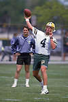 Green Bay Packers quarterback Brett Favre (4) throws a pass as assistant coach Steve Mariucci looks on during an NFL football mini-camp on June 2,1993. (Photo by David Stluka)