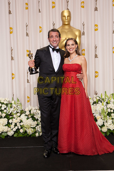 "Oscar®-winning actor Jean Dujardin, winner for Performance by an Actor in a Leading Role for his role in ""The Artist"", poses backstage with Natalie Portman. The 84th Annual Academy Awards Awards® is broadcast live on the ABC Television Network from the Hollywood and Highland Center, in Hollywood, CA, Sunday, February 26, 2012..*Editorial Use Only*.oscars award trophy winner full length red dress strapless polka dot black tuxedo.CAP/A.M.P.A.S./NFS.©A.M.P.A.S. Supplied by Capital Pictures."