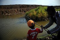 A father and son fishing in the shadow of the earthen dam which is struggling to contain the mud flow. Since May 2006, more than 10,000 people in the Porong subdistrict of Sidoarjo have been displaced by hot mud flowing from a natural gas well that was being drilled by the oil company Lapindo Brantas. The torrent of mud - up to 125,000 cubic metres per day - continued to flow three years later.