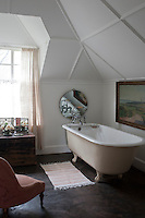 A vintage bath tub stands in one corner of the colonial-style batten-and-panel bathroom