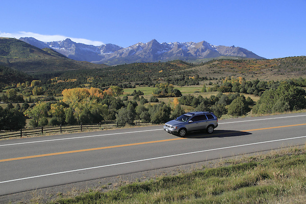 Station wagon on highway with the Sneffels Range, near Telluride, Colorado, USA.