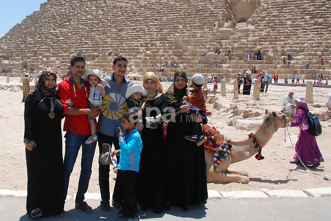 Egyptians poses for a photograph in front of the Giza pyramids, on the third day of Eid al-Fitr holiday which marks the end of the Muslim holy month of Ramadan, in Cairo on July 19, 2015. Photo by Amr Sayed