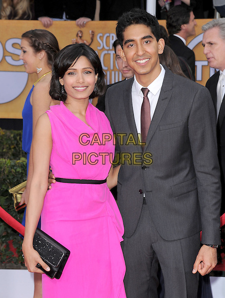 Freida Pinto (wearing Roland Mouret) & Dev Patel .Arrivals at the 19th Annual Screen Actors Guild Awards at the Shrine Auditorium in Los Angeles, California, USA..27th January 2013.SAG SAGs half length pink dress grey gray suit couple black clutch bag draped.CAP/DVS.©DVS/Capital Pictures.