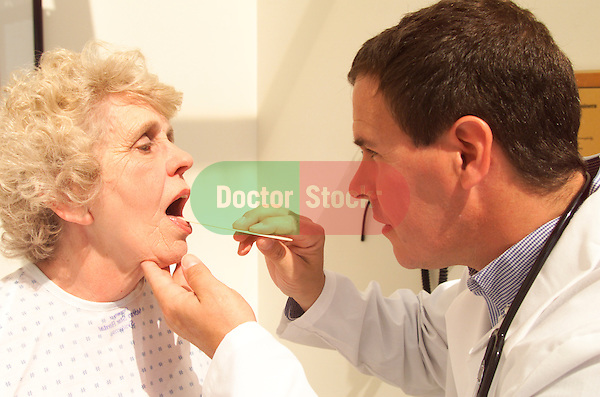 young male doctor conducting a routine examination of an older, elder female patient, looking in mouth using tongue depressor