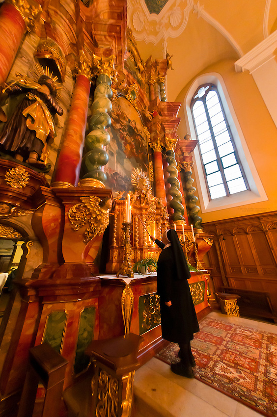 A nun lighting candles for Sunday Mass, Monastery of Our Lady of Offenburg (Capuchin Monastery), Offenburg, Baden-Württemberg, Germany