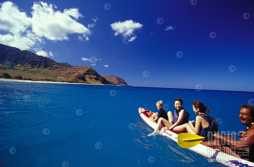 Group of visitors with guide and young boy paddling a dolphin watching kayak in clear blue water off Makua Beach, West Side of Oahu, Hawaii