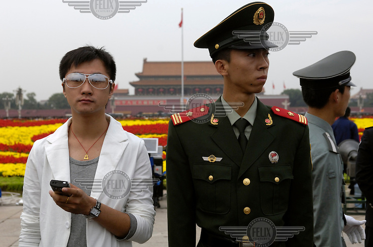 Young man next to a soldier on guard in Tiananmen Square during National Day celebrations.